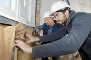 Workers Insulating House Walls
